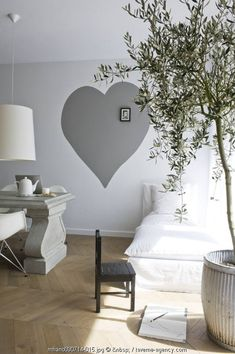 A grey heart painted on the wall, an olive tree, white bed linens...I'm at home thank you very much