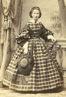 1861-1865, Lovely plaid day dress for visiting or shopping with really full sleeves & tighter undersleeves; solid sleeve caps that extend to bodice center like low lapels and a wonderful hat!  Love this design.  (The small dainty figure helps!)