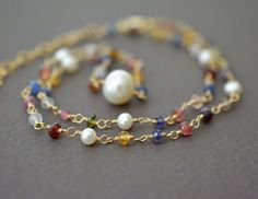 This multi gemstone necklace has at its center a large white freshwater pearl. It is the focal point of a meticulously hand-wrapped, rosary-style, gemstone chain. Every tiny stone is individually wrapped in 14K gold-filled wire and they are interspersed with smaller freshwater pearls. The gemstones are in soft, muted colors and include: pink sapphires, blue sapphires, green amethyst, citrine, iolite and more. It fastens with a gold-filled lobster clasp and 2 inch extender chain.  Length: 17…