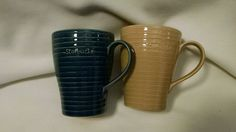 1 blue and 1 tan mug, both 12 oz. Printing is worn a little on the blue one. No chips or cracks.