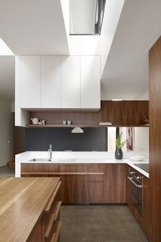 Beautiful modern kitchen with warm wood, open shelving, clean sleek white counters.