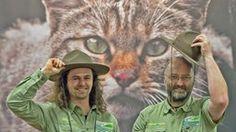 Zwei Ranger vom Natoinalpark Eifel posieren vor dem Bild einer Wildkatze