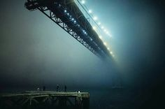 Photo by André Sanano @andresanano using the Fujifilm X100T - I couldn't really believe my eyes when I first saw this image. No it's not the Manhattan bridge neither the golden gate bridge, it is the Ponte 25 de Abril in Lisbon, Portugal  The sense of scale is just jaw dropping, the way the fog engulf the first pillar and how the dock structure echo the metal structure above. How fragile the fishermen looks in the fog, on the edge of a bottomless pit. The glowing lights even seems to b...