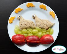 2 dinosaur peanut butter sandwiches with candy icing eyes, sliced green grapes and sliced red apple, 5 mini dinosaurs made out of cheddar cheese made using a small dino cookie cutter. SUPER EASY!