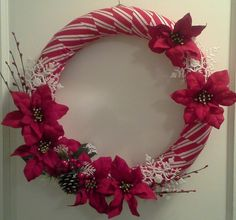 Pool noodle foam wreath form decorated with candy cane ribbon, red poinsettias, berry branches and snowflakes.
