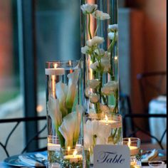 Some of the centerpieces will be a trio of cylinder vases with submerged fuchsia phalaenopsis orchids, light pink spray roses and dark purple waxflowers surrounded by mercury glass LED votives.