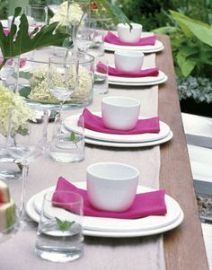 In the center of the table, single philodendron leaves partner with clusters of delicate 'Limelight' hydrangea in simple glass containers. Sprigs of fresh mint in the glasses nod to the garden theme, while vibrant pink napkins add a pop of color to the white place settings.   - CountryLiving.com
