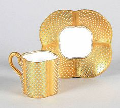 Coalport 'jewelled' cup and saucer Circa 1900 of quatrelobed form, the gilt ground applied with alternate 'jewelled' panels in white and turquoise, printed green marks
