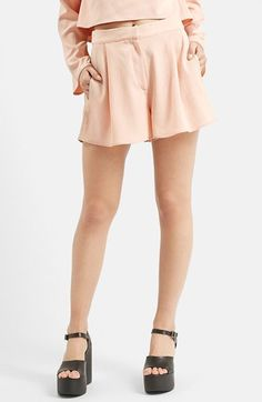 Free shipping and returns on Topshop 'Hitch' Flippy Shorts (Nordstrom Exclusive) at Nordstrom.com. A lovely peach hue softens textured crepe shorts defined by gentle front pleats and flippy hems. A smocked back waist eases the pull-on fit.