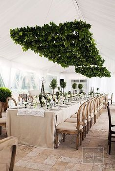 For an elegant, refined look, hang garlands of greenery above dinner tables in a crisp lattice- or grid-style format.