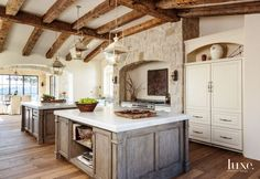 Mediterranean kitchen features a vaulted ceiling lined with rustic wood beams and distressed gray carriage lanterns hanging over side by side islands topped with carrera marble atop a wide plank wood floor. Wood Kitchen Island, Kitchen Cabinetry, Floors Kitchen, Stone Kitchen, Kitchen Reno, Rustic Wood Floors, Wood Beams, Layout Design, Design Ideas