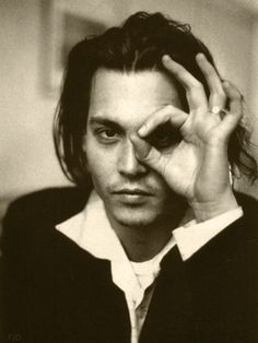"""Johnny Depp showing the all seeing eye symbol.  And the  """"3""""  fingers holding the shape of the number """"6"""" 3 representing the statement of claiming triple """"6""""s."""
