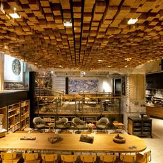 """Starbucks concept store in Amsterdam. """"Design director Liz Muller assembled a team of local artists and craftsmen to create features that include repurposed oak furniture, antique Delft tiles and wall coverings fashioned from the recycled inner tubes of old bicycle tires""""."""