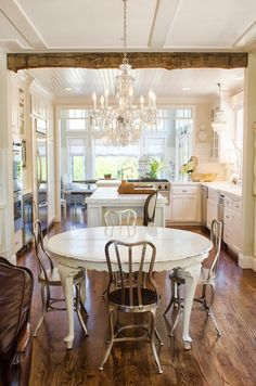 Love the table & chairs, exposed beams, gas cooktop, island.