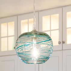 Swirling Glass Globe Mini Pendant Light Light patterns dance on the walls and ceiling from the swirling patterns on this glass globe mini pendant light. Golden Bronze swirls on a slightly iridescent globe or Aqua swirls on clear glass. Each one is uniquely hand blown.