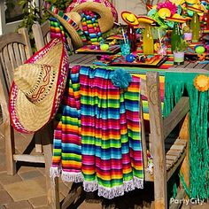 Cinco de Mayo Tablescape ~ Create a south-of-the-border setting for your fiesta! Invite your amigos over to fiesta like theres no mañana! Set the scene for fun by stringing up a colorful bandana bunting over a table styled with sombreros, serapes and Mexcian soda bottles. Mini sombreros, maraca favors and moustache straws take the table from ordinary to ¡olé!