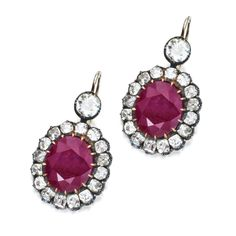 PAIR OF GOLD, SILVER, RUBY AND DIAMOND PENDANT-EARRINGS. Set with 2 oval rubies weighing 19.67 carats, framed and surmounted by old mine diamonds weighing approximately 7.90 carats.