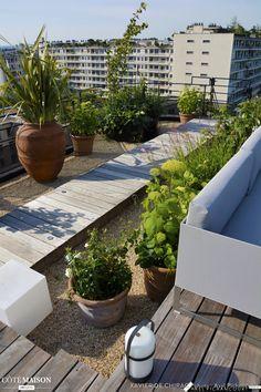 Une terrasse avec des fleurs, des feuilles, des fruits qui sont plantées dans des massifs généreux, un esprit campagne, jardin sauvage..