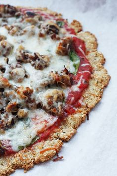 Paleo Pizza Crust - 1/2C flax meal, 1/4C coconut flour, 1/4Chemp seed or almond flour, 1/2tsp garlic powder, 1/2tsp oregano, 1/2tsp baking powder,  2 eggs. Preheat 350. Combine all dry ingreds, mix well. Add eggs, stir til dough forms.  Press or roll 10″ on a parchment lined pan. Bake :12 min.  Remove, add toppings, bake another :18-20 min until crust is golden brown