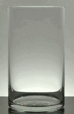 Clear Glass Cylinder Vase 6in.  Floating candles on top.  greens and/or berries underneath.