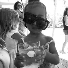 """Khloe Kardashan posted a funny picture of her niece North West wearing a crooked pair of sunglasses and holding up a drink with the caption, """"MOOD."""""""