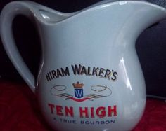"Vintage McCoy Hiram's Walker Bourbon Pitcher 1970s $15.00 | This Walker bourbon pitcher is made by McCoy with USA mark on bottom. This pitcher is grey with logo in red and black, which looks fabulous on shiny, glazed grey color. The advertising logo says Hiram Walker's Ten High  A True Bourbon in red writing. It has small chip on one side near spout. The rest is in great condition!  Dimensions:  -- 6 3/8"" height -- 7"" length from spout to handle  -- 3 5/8"" width"