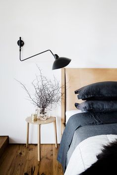 This modern bedroom features a black wall lamp, and a wood bed frame with a leather headboard. Trendy Bedroom, Modern Bedroom, Bedroom Black, Contemporary Bedroom, Modern Wall, Home Decor Bedroom, Bedroom Wall, Design Bedroom, Bedroom Ideas