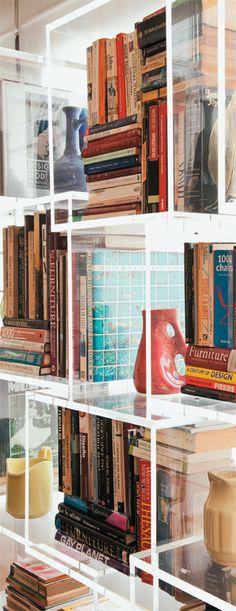 A estante de acrílico tem nichos iguais, mas fixados de maneira desencontrada para criar interesse e expor vasos e livros de modo dinâmico.
