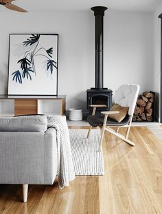 Living room with light grey sofa and rug, large art work, and a black wood burning fire place