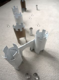 Marble obstacle course game- the rules: 6 obstacles made of toilet paper rolls (tunnels, gradient tunnels, gates, goal tower...), arrange it with some clay figures (some extra points).  play by turns, it means more fun. Reach goal tower and win.