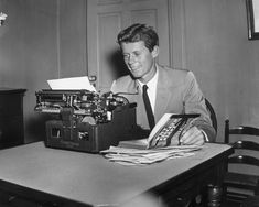 Future American president John F Kennedy, sits at a typewriter, holding open his published thesis, 'Why England Slept' ~ 1940