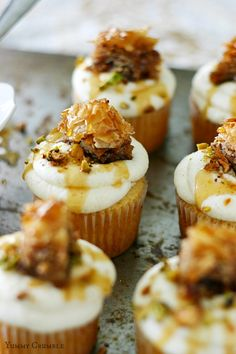 Baklava cupcakes topped with cinnamon mascarpone whipped frosting, chopped pistachios, and honey syrup