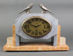 Lot 802, A French Art Deco 8 day timepiece with oval gilt dial and Arabic numerals marked Maquer Lens, contained in a grey and pink marble case surmounted by 2 figures of birds, est £80-120