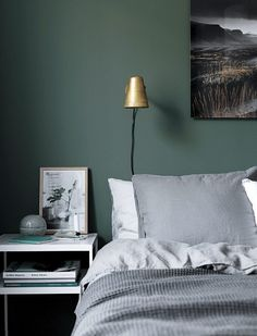 Dark green walls in the bedroom of a calm Swedish space