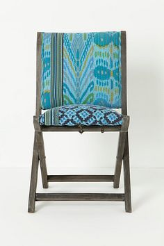 Anthro folding chairs - DIY something similar by covering wooden folding chairs with fun fabric & cushions.