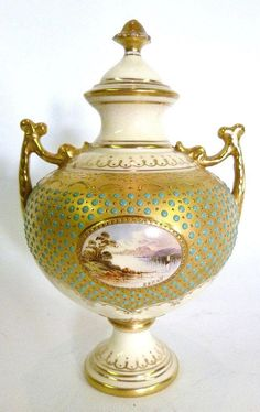 A Coalport Jewelled Covered Vase, of globular form decorated with a reserve depicting a lake scene upon a circular pedestal base, 15cms high