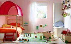 A small children's bedroom furnished with a pine bed with posts and a pink canopy. Shown together with wooden storage boxes on wheels filled with toys.