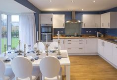 Interior designed kitchen diner with white units / oak worktop and french blue wall.  This is so interesting because this is the same set of table and chairs used in the previous set photo, in a different house on the development.