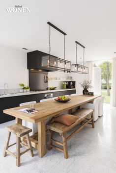 Serene, open plan and modern can you get? Love the new + old wood table and benches, clean hood and shelf lines, mix of natural stone, glass, linen, reclaimed wood, black+white. Lamp looks nice, probably casts a harsh light though