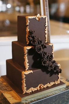 Three tier square chocolate wedding cake with gold trim and cascading chocolate roses...      ᘡղbᘠ