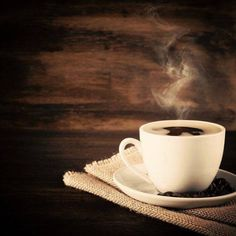 steaming coffee in front of wooden background