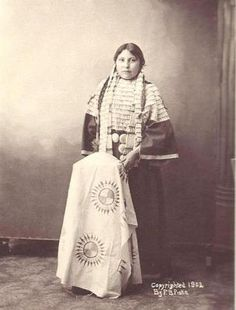 """Girl with Cloth —From the end of girl's pigtails hang a double set of yarn wrappings. The cape is dentalia shells. The rather elaborate hair pipe front piece is divided by spacers and strands of brass trade beads The belt or """"drag"""" of silver conchos were manufactured by whites for trade with Indians near the end of the 19th Century. 1902. 6 ¼ X 8 ¼ inch mounted on archive rag board."""