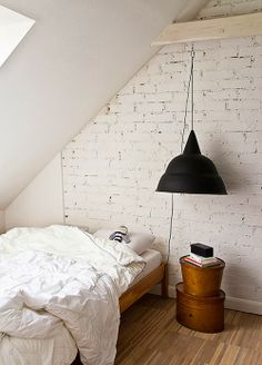 Bedroom with white exposed brick.