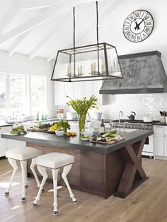 Modern White Kitchen  Both the Vassaro chandelier by Gregorius/Pineo and the metal hood remind Hoefer of a classic French mansard roof. She designed the A la Reine stools with goat's feet.