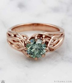 Embracing Tree Branch Engagement Ring in 14k rose gold and a beautiful green diamond center stone. This design is custom made just for you in the metal and solitaire stone you want. Start the fun and easy design process at krikawa.com