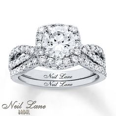 This bridal set for her from the Neil Lane Bridal® collection includes an engagement ring showcasing a dazzling cushion-cut diamond framed in round diamonds. Additional round diamonds sparkle along the band of the engagement ring and the matching contoured wedding band. The bridal set has a total diamond weight of 2 1/2 carats and is styled in 14K white gold. Neil Lane's signature appears on the inside of both rings. Diamond Total Carat Weight may range from 2.45 - 2.57 carats.