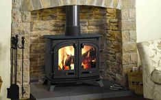 Surrounded by a stone fireplace this wood-burning stove will look at home in a traditional setting. Exe wood-burning stove, from - Wood Stove Surround, Wood Stove Hearth, Stove Fireplace, Fireplace Wall, Best Wood Burning Stove, Log Burning Stoves, Foyers, Multi Fuel Stove, Freestanding Fireplace