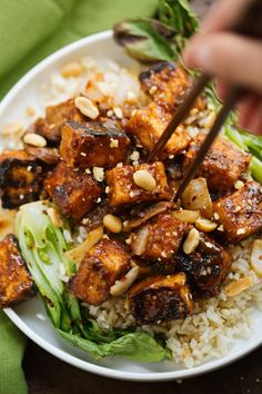 """A super flavorful spicy peanut tofu stir fry! The tofu is tossed in a homemade thai-style peanut sauce and is crispy without frying! I'm pan sautéing my tofu along with shiitake mushrooms and sliced onions. Serve it on a bed of brown rice, quinoa, or on it's own."""