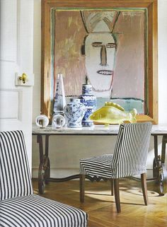 traditional eclectic vignette--ticking stripe chairs, large art, blue and white ceramics