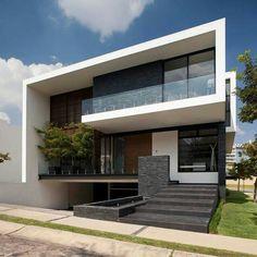 Casa com beiral e contorno branco, guarda corpo branco, vidros transparentes e escada e detalhe em pedras cinzas.
